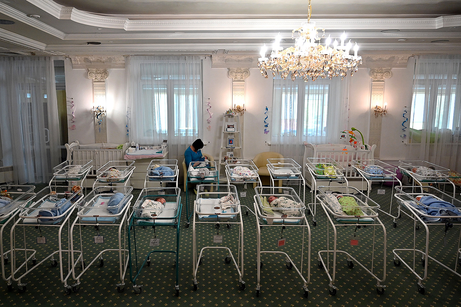 A nurse cares for surrogate-born newborns at Kiev's Venice Hotel on May 15. More than 100 babies born to surrogate mothers have been stranded in Ukraine as their foreign parents can't collect them because of border closures imposed during the pandemic. SERGEI SUPINSKY/AFP via Getty Images