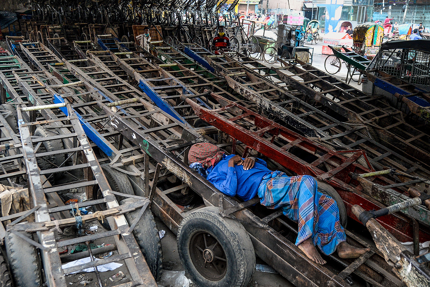 A worker sleeps on a pushcart in Dhaka, Bangladesh, on May 1, International Workers' Day. MUNIR UZ ZAMAN/AFP via Getty Images