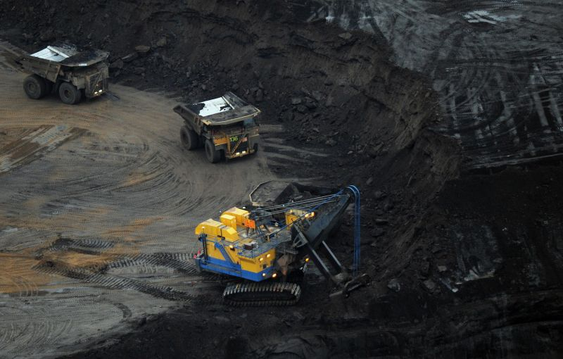 An excavator loads a truck with oil sands.