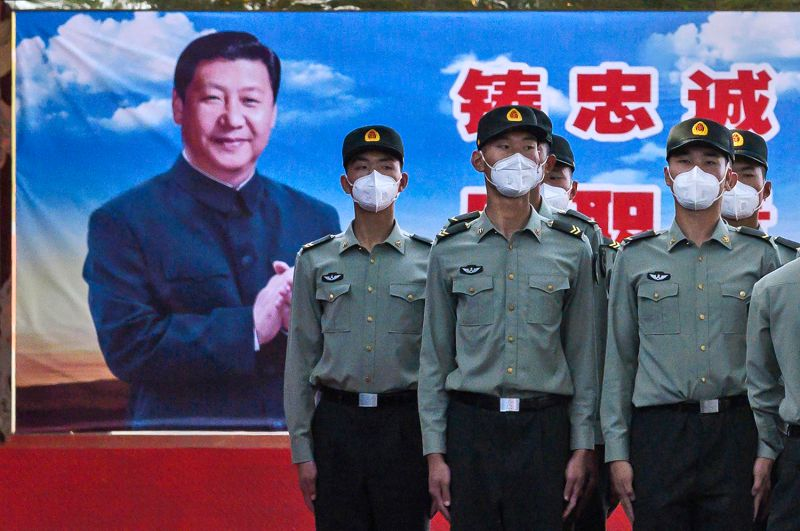 People's Liberation Army soldiers stand at attention in front of photo of Chinese President Xi Jinping in Beijing on May 20.