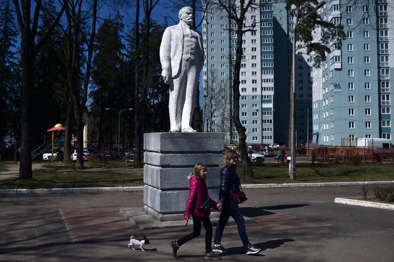 People walk past a monument to Vladimir Lenin in Minsk, Belarus, on the 150th anniversary of Lenin's birth on April 22.