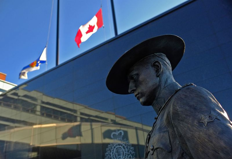 The flags of Nova Scotia and Canada fly at half-staff outside the Nova Scotia Royal Canadian Mounted Police headquarters in Dartmouth, Nova Scotia, on April 19.