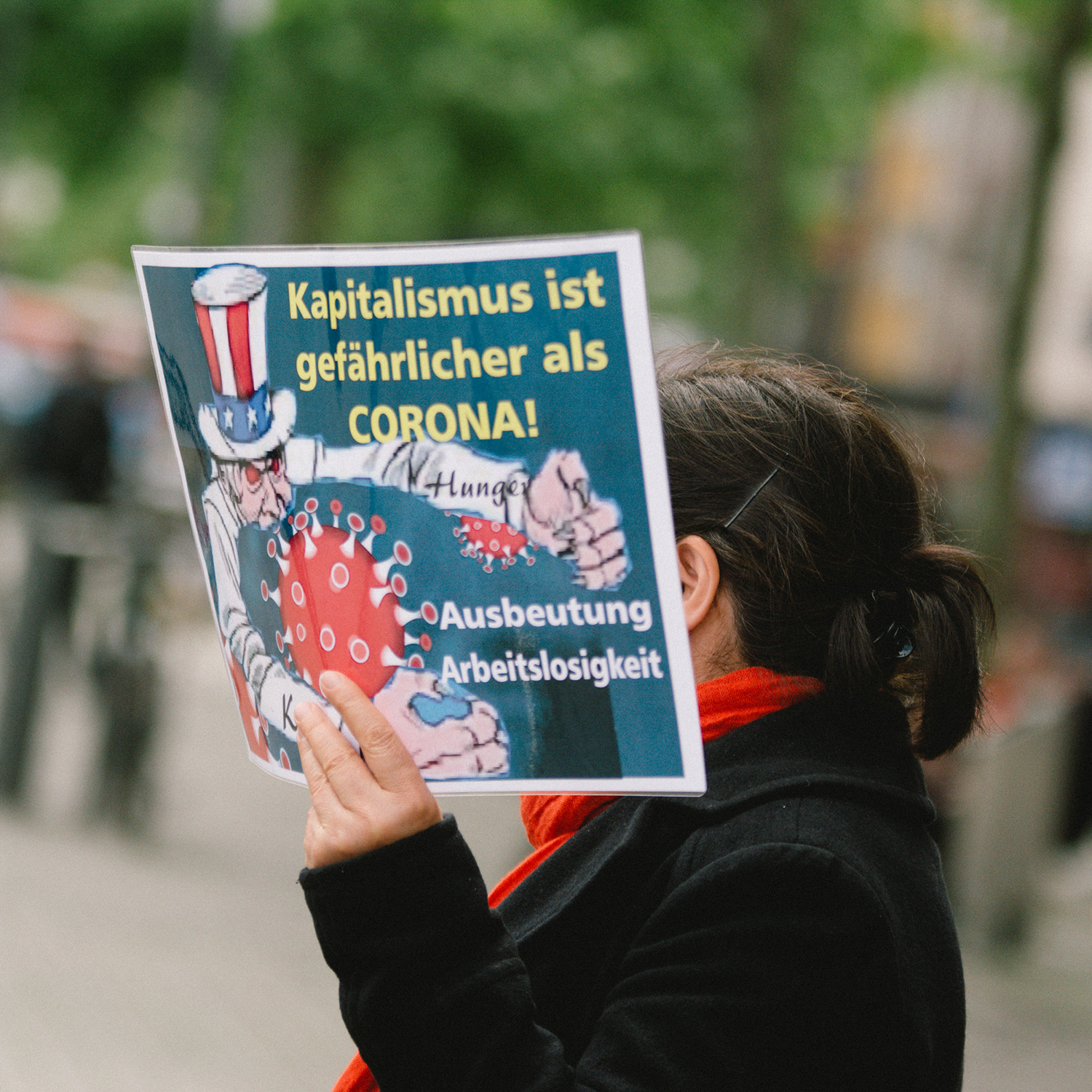 "A placard with ""capitalism is more dangerous than coronavirus"" is seen at a demonstration in Cologne, Germany, on May 1."