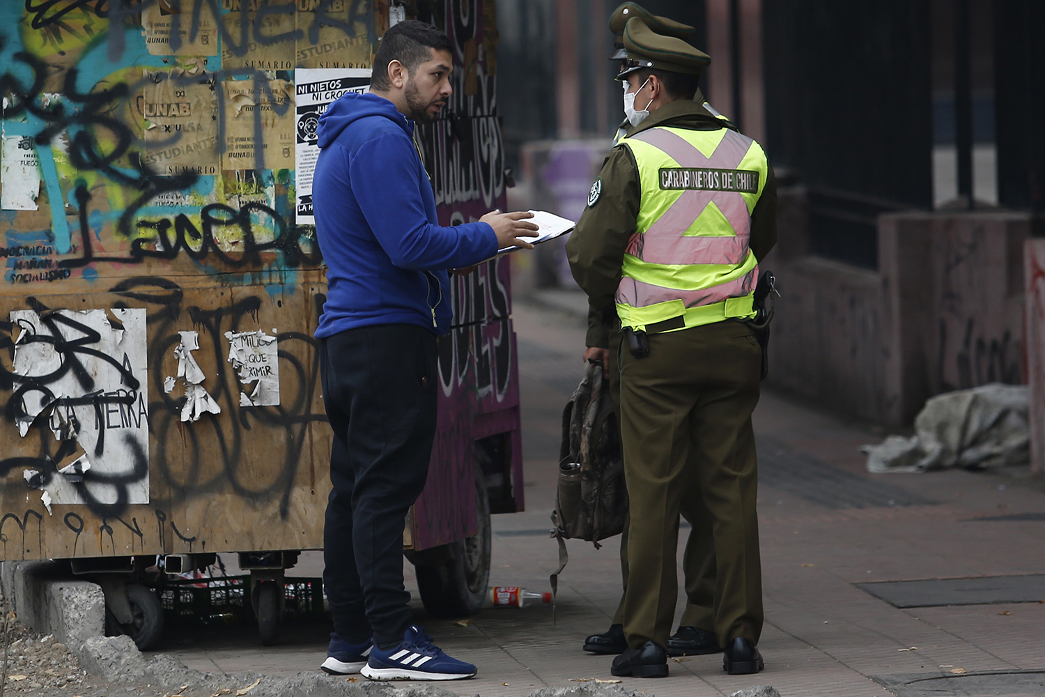 Police officers check the papers of a man before accessing the quarantine area during the first day of the lockdown in seven communes of Santiago, Chile, on March 27.
