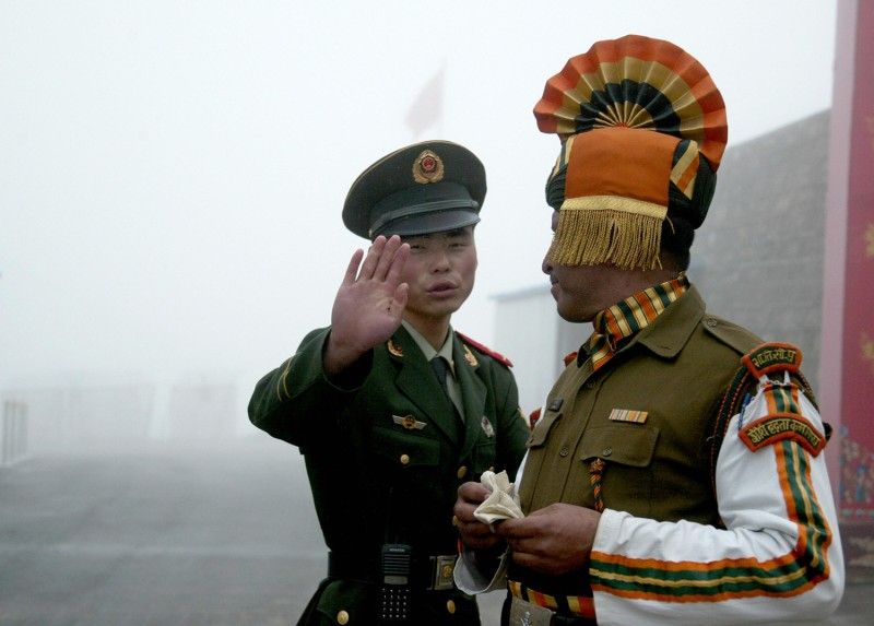 A Chinese soldier gestures as he stands near an Indian soldier on the Chinese side of the ancient Nathu La border crossing between India and China on July 10, 2008.