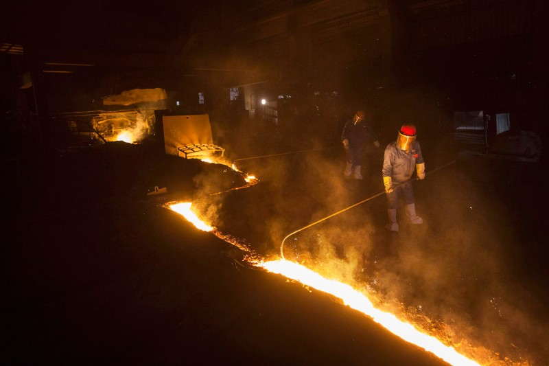 Workers move molten iron at a furnace in the production area of the Zhongtian Steel Group Corp. in Changzhou, China, on May 13, 2016.