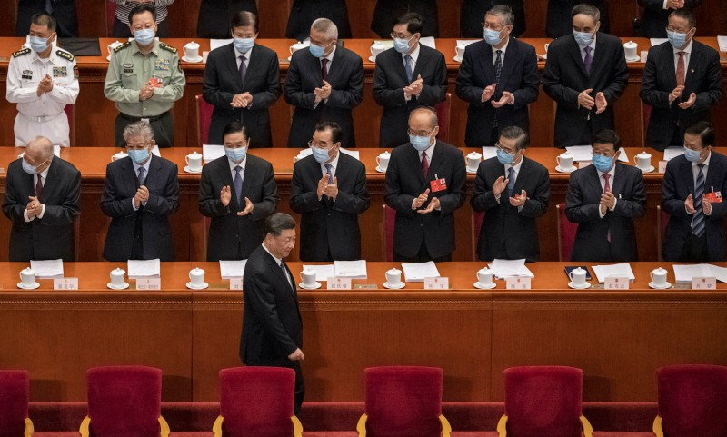 Chinese president Xi Jinping is applauded by delegates wearing protective masks as he arrives at the opening of the National People's Congress on May 22, 2020 in Beijing.