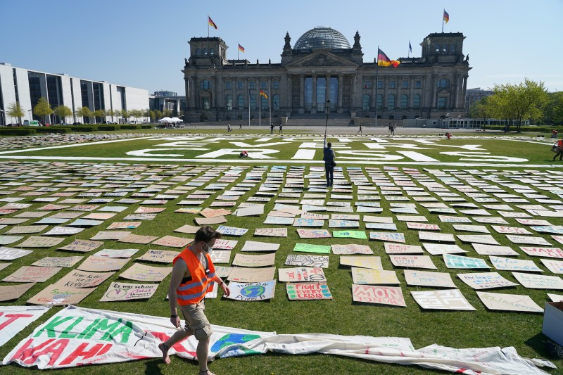 An activist with the Fridays for Future movement helps to pin thousands of protest signs and banners to the lawn in front of the Reichstag during the novel coronavirus crisis on April 24, 2020 in Berlin, Germany.