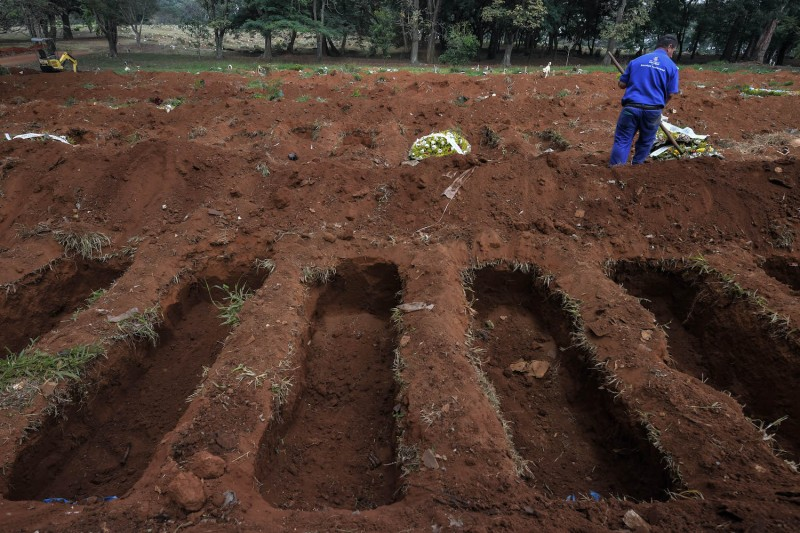 An employee is seen among freshly dug graves at the Vila Formosa cemetery, in the outskirts of Sao Paulo, Brazil on May 20, 2020.
