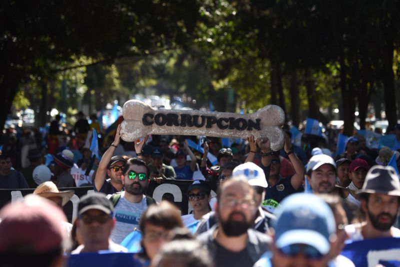 """Demonstrators hold up a giant doggie biscuit reading """"corruption"""" during a rally in support of the United Nations International Commission Against Impunity in Guatemala City on Jan. 12, 2019."""