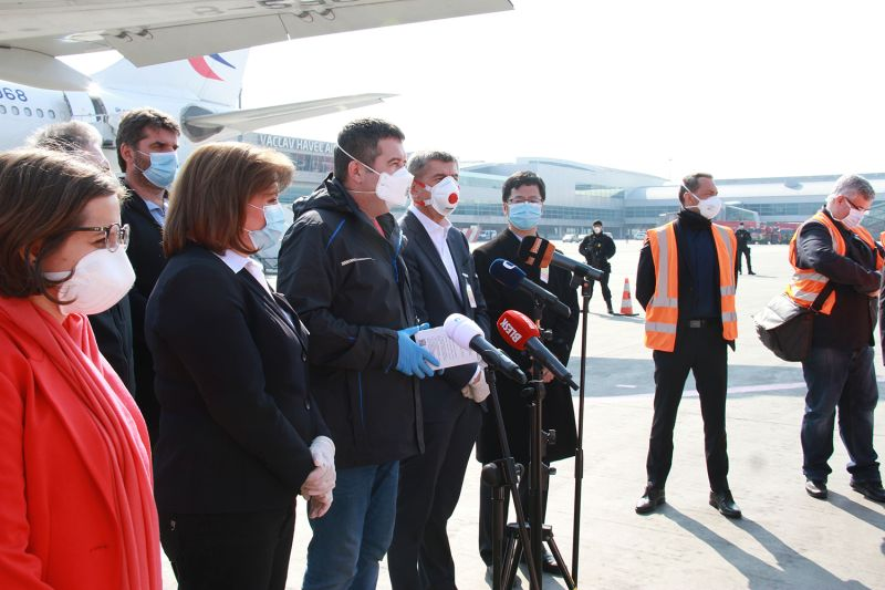 Czech Deputy Prime Minister and Interior Minister Jan Hamacek (third from left) speaks at Prague Airport in the Czech Republic on March 20. A China Eastern Airlines plane carrying 1.1 million respirators purchased by the Czech Republic from China is behind him.