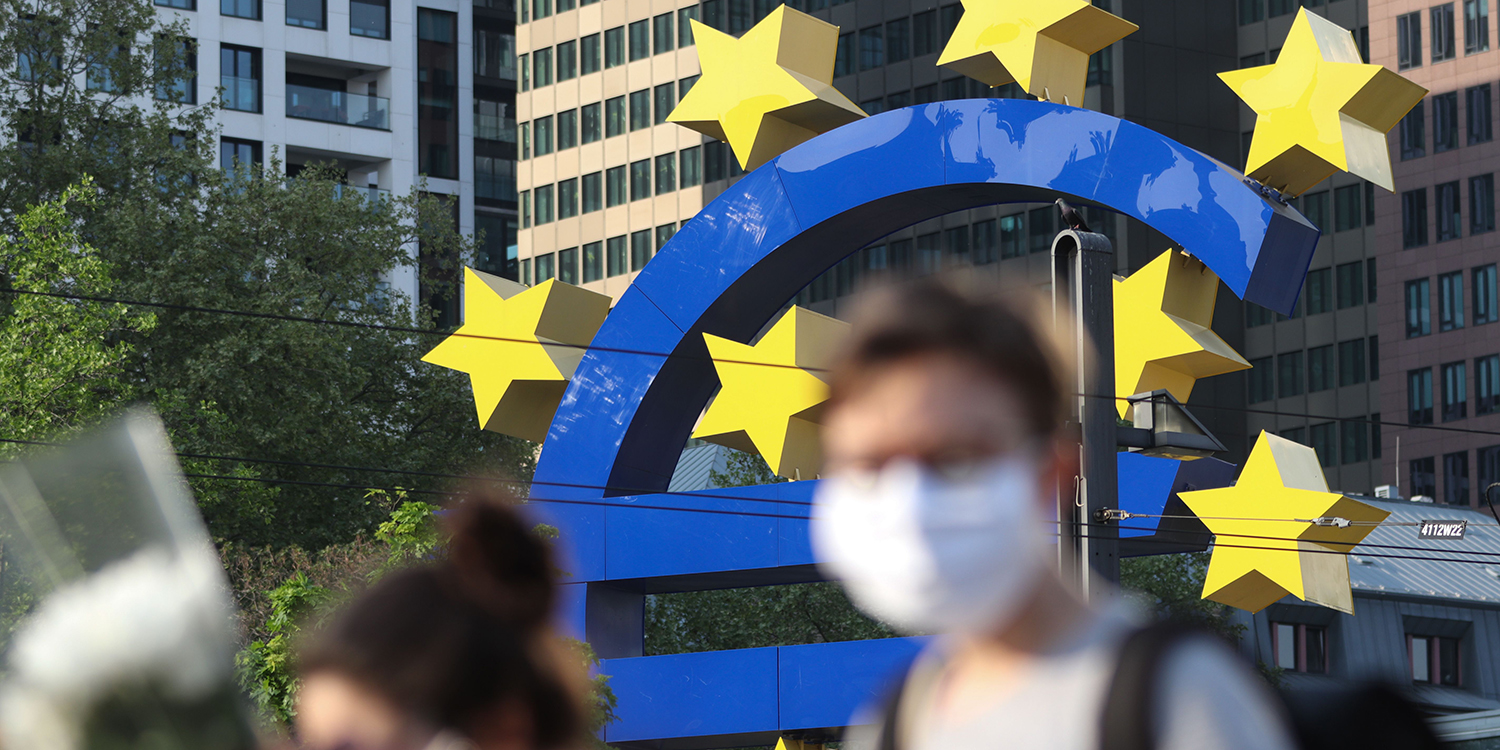 People wearing face masks walk in front of a big euro sign in front of the European Central Bank headquarter in in Frankfurt on April 24.