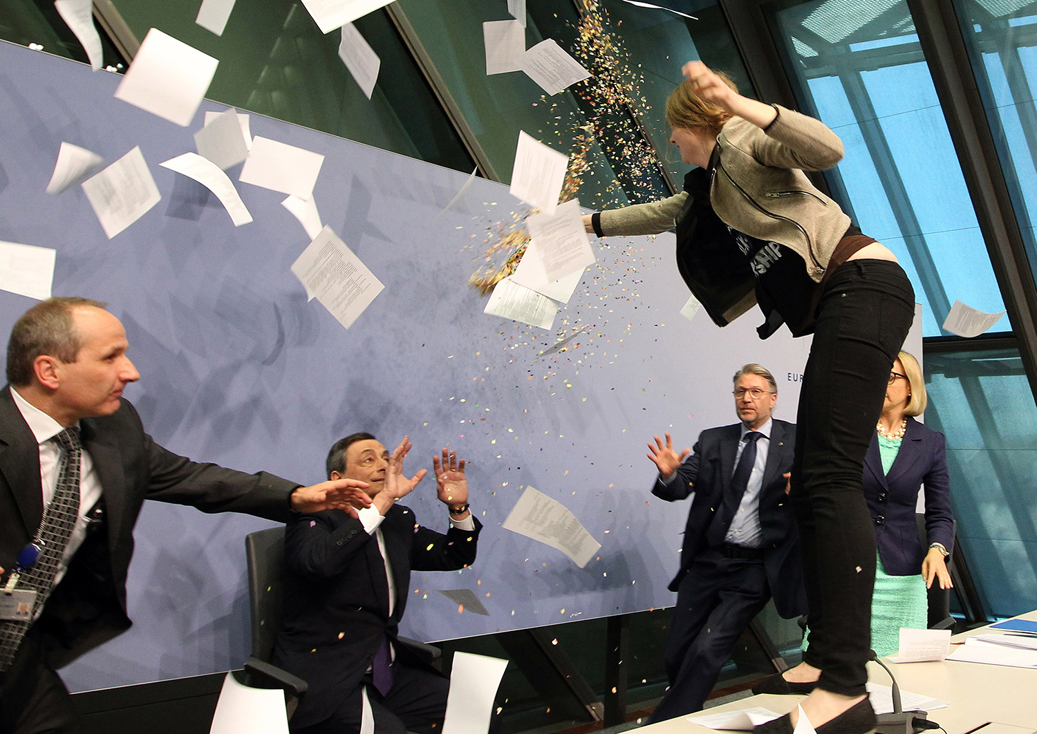 "A woman jumps on the table, throwing papers and confetti, and calling for an ""end to the ECB dictatorship"" as she disrupts a news conference in Frankfurt, Germany, on April 15, 2015."