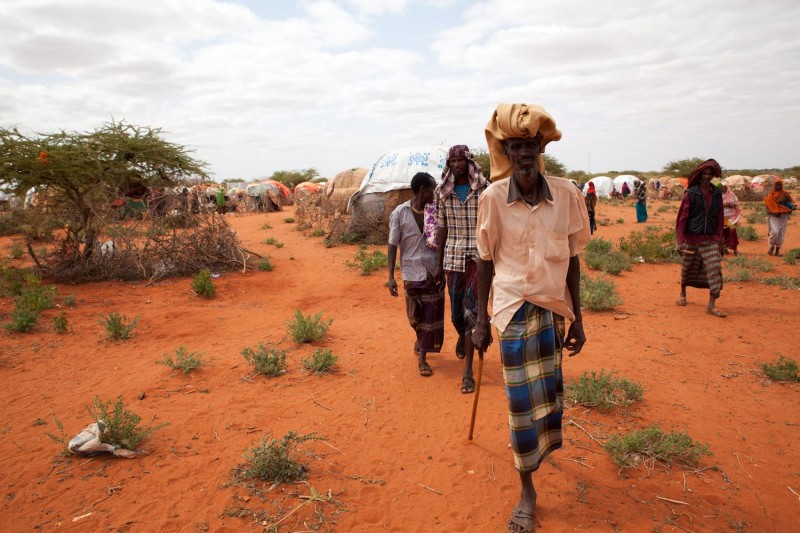 People displaced by drought walking at a displaced persons camp.