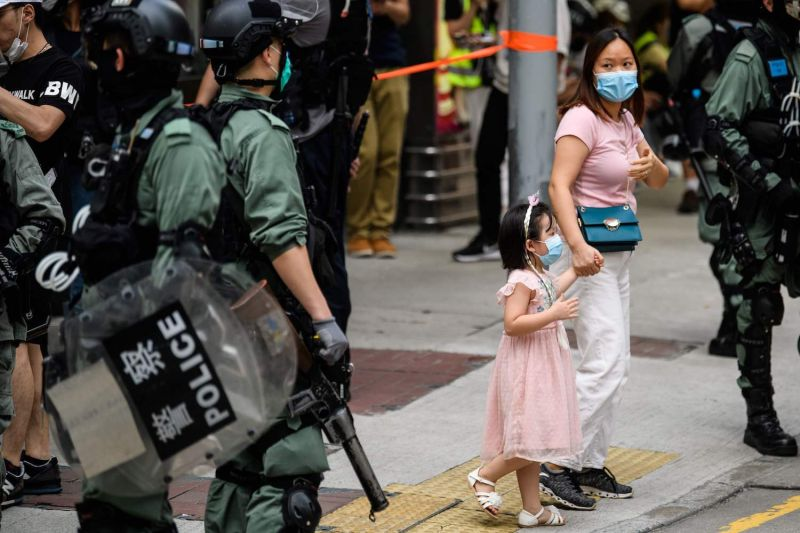 A woman and child walk past riot police standing guard on a street in the Mongkok district of Hong Kong on May 27, as the city's legislature debates over a law that bans insulting China's national anthem.
