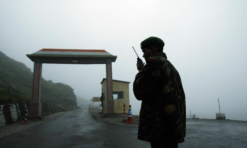 An Indian soldier communicates with colleagues on a walkie talkie at Nathula Gate, leading to the Nathu La border crossing between India and China.
