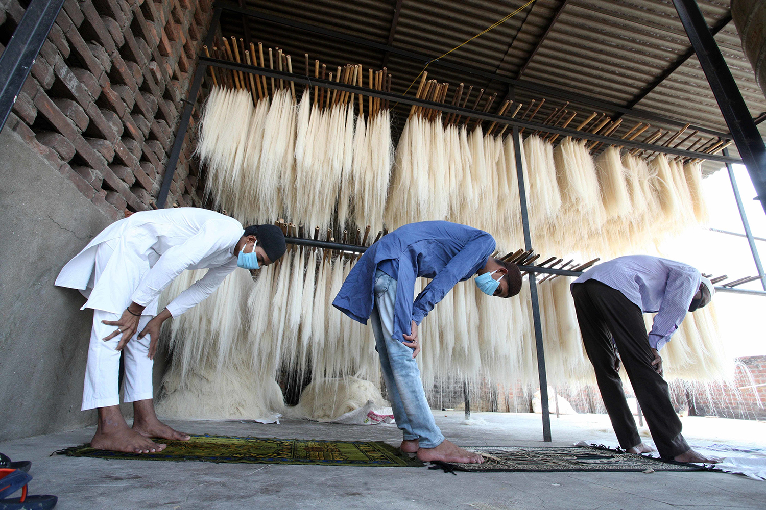 Muslim workers offer Friday prayers as they stand near vermicelli used to make traditional sweets popular during Ramadan, amid a nationwide lockdown as a preventive measure against coronavirus, at a factory in Prayagraj, India on May 1.