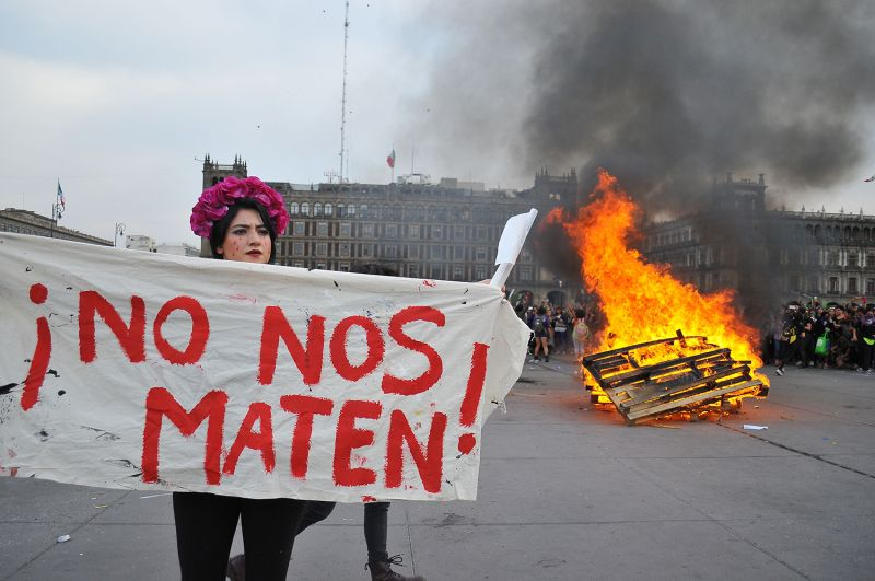 "A Mexican woman holding a sign that reads ""Don't kill us"""