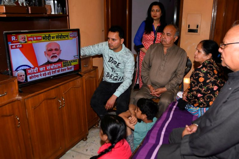 A family watches Indian Prime Minister Narendra Modi's address to the nation on a television at their home in Amritsar on March 24.