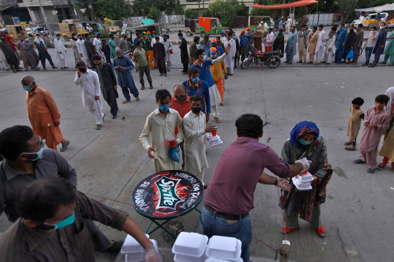 Volunteers distribute food boxes and a traditional sweet drink among people for breaking their Ramadan fast in Rawalpindi, Pakistan, on May 3.