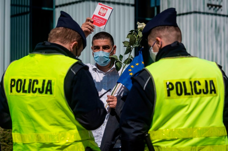 A man holds a copy of the Polish Constitution as police officers check his ID card after he took part in a protest in Warsaw, Poland, on April 30.