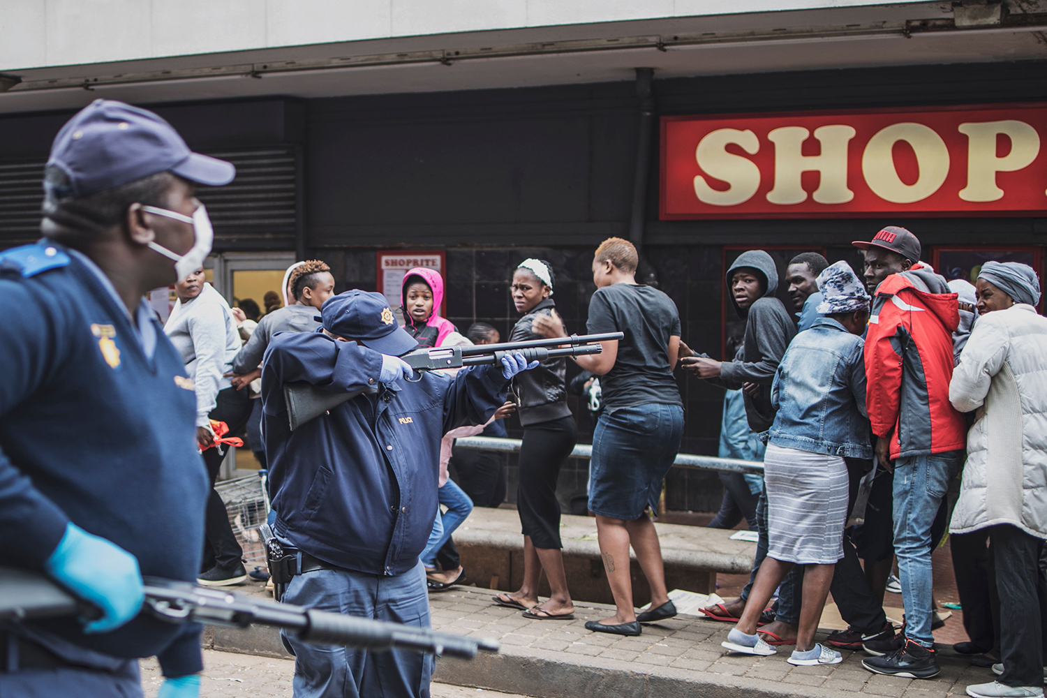 A South African policeman points his pump rifle to disperse a crowd of shoppers in Yeoville, Johannesburg, on March 28 while trying to enforce a distancing measures outside a supermarket amid concern about the spread of the coronavirus.
