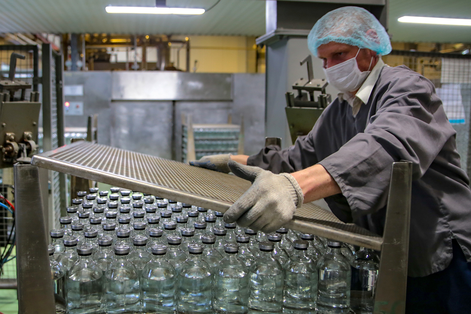 A man in a facemask works at a production facility of the pharmaceutical company Escom, which manufactures saline solution, glucose solution, and other infusion and injection solutions in Stavropol, Russia, on May 6. The factory has moved to round-the-clock production during the pandemic. Alexander PogozhevTASS via Getty Images