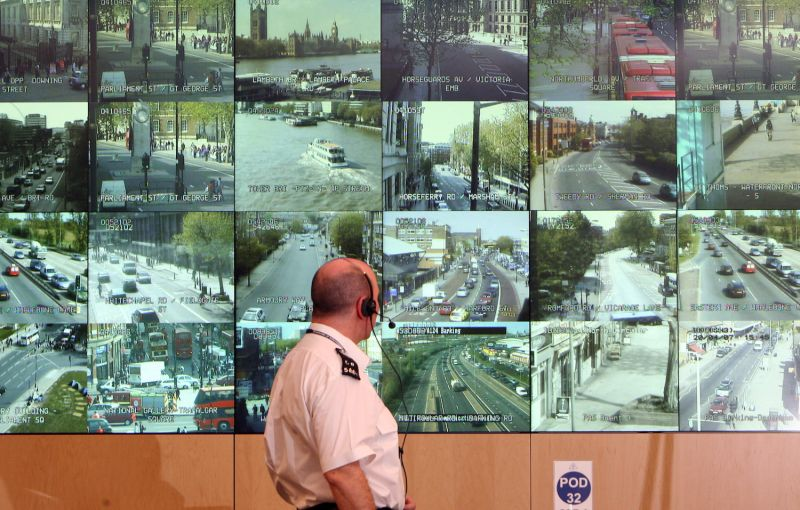 A police officer watches television monitors showing a fraction of London's CCTV camera network.