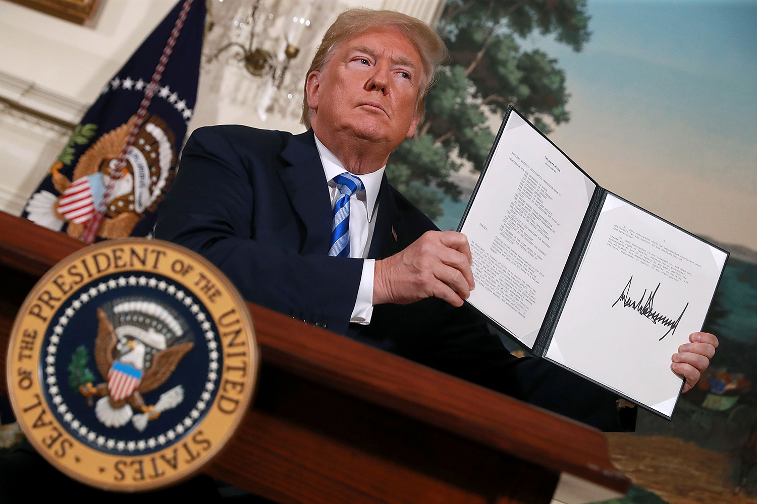 U.S. President Donald Trump holds up a memorandum at the White House in Washington that reinstates sanctions on Iran after he announced his decision to withdraw the United States from the 2015 Iran nuclear deal on May 8, 2018.