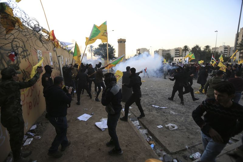 U.S. soldiers intervene against Iraqi protesters carrying flags of Kataib Hezbollah as they storm the U.S. Embassy.