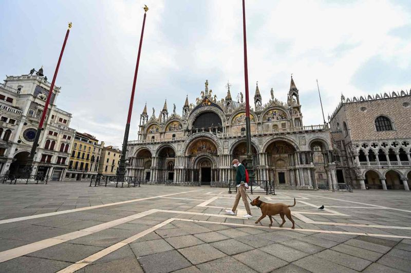 A man wearing a face mask walks his dog across a deserted St. Mark's Square in Venice, Italy, on May 13.
