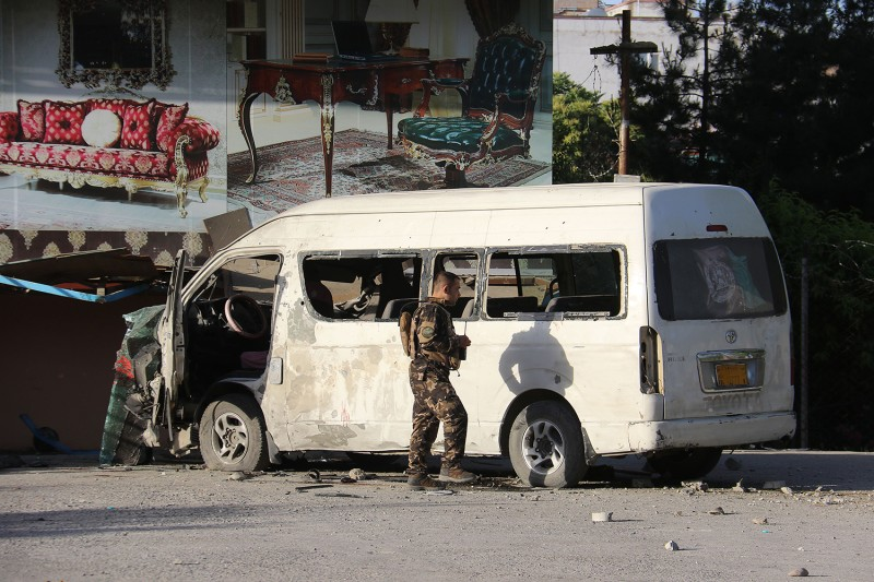 An Afghan security officer investigates a damaged vehicle that was carrying employees of Khurshid TV at the site of a bomb blast that killed a journalist in Kabul on May 30.