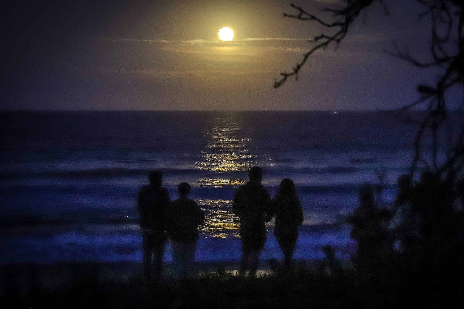 """Spectators gather to watch a full """"strawberry moon"""" rise above the ocean on Narrawallee Beach near Mollymook, Australia, on June 6. DAVID GRAY/AFP via Getty Images"""