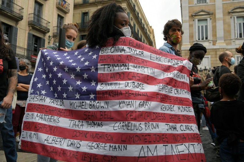 A protester holding a U.S. flag takes part an anti-racism demonstration in Barcelona