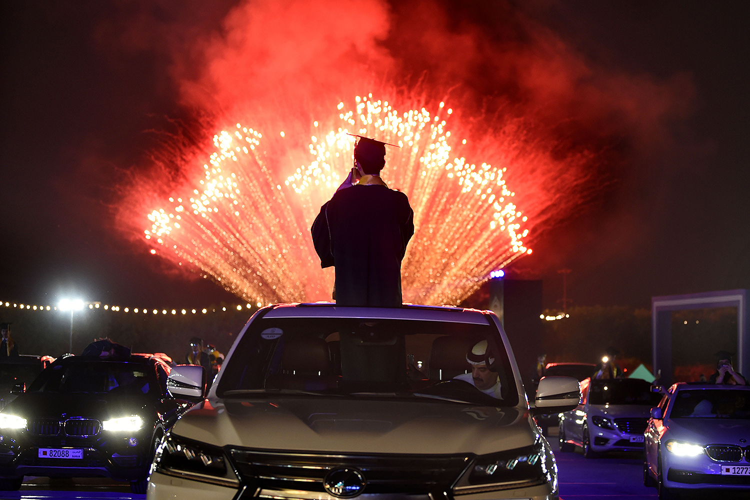 Following a socially distanced graduation ceremony, high school seniors and their families watch fireworks at the Bahrain International Circuit car racing track in Sakhir, Bahrain, on June 10. MAZEN MAHDI/AFP via Getty Images