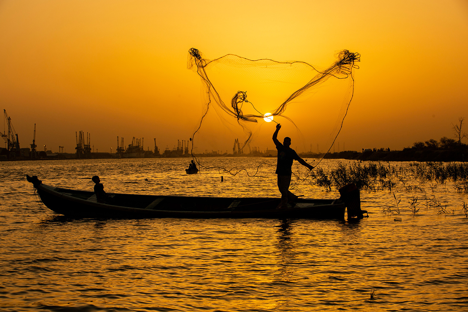 A fisherman casts his net at sunset in the Shatt Al-Arab River in the southern Iraqi city of Basra on June 12. HUSSEIN FALEH/AFP via Getty Images