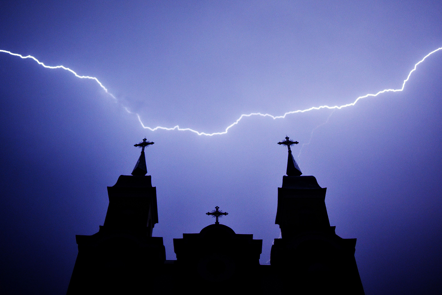 Lightning strikes are seen above a Catholic church during a thunderstorm in the village of Kreva, Belarus, on June 9. SERGEI GAPON/AFP via Getty Images
