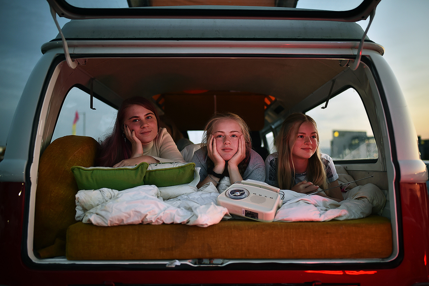 "Using a classic radio to listen to the audio, sisters Rosie, Grace, and Alex McQueen watch the movie ""Grease"" at a drive-in theater in Belfast, Northern Ireland, on June 13. Charles McQuillan/Getty Images"