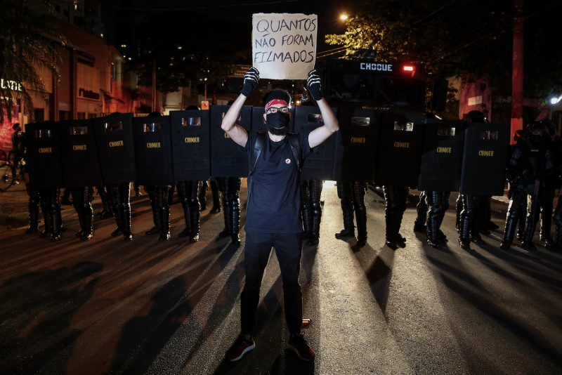 """A protester holds a sign that reads """"How many were not filmed"""" in Portuguese stands in front of a riot police squad during a protest on June 7 in Sao Paulo, Brazil."""