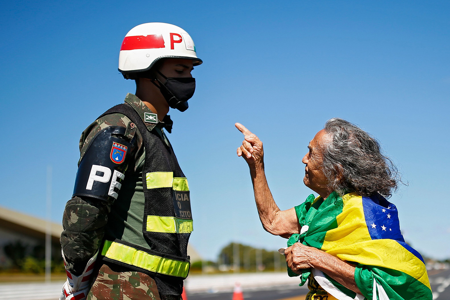A supporter of Brazilian President Jair Bolsonaro speaks to a soldier as she takes part in a protest against the coronavirus lockdown outside the army headquarters in Brasilia on June 14. SERGIO LIMA/AFP via Getty Images