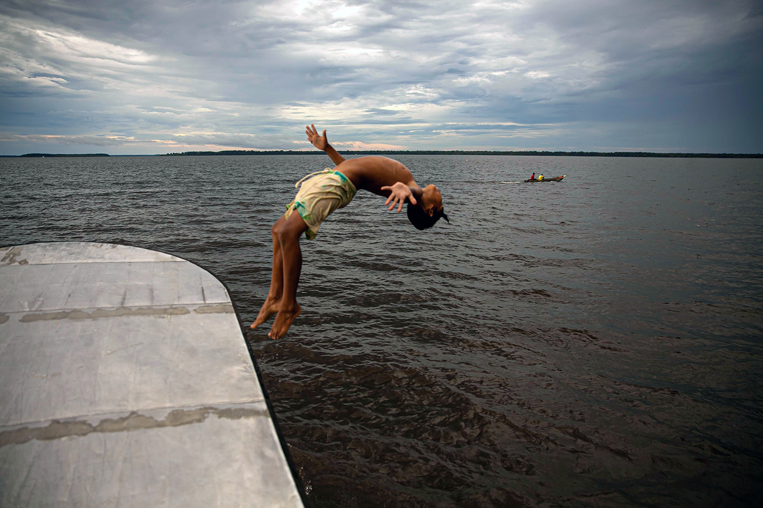A child jumps into the water at Melgaco Bay, southwest of Marajó Island in Brazil, on May 29. TARSO SARRAF/AFP via Getty Images