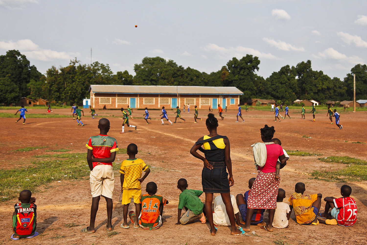 Women and children watch a football game in Bossangoa on June 7, 2019. The tournament was organized by the charity War Child to bring the community together and encourage social cohesion following years of fighting.