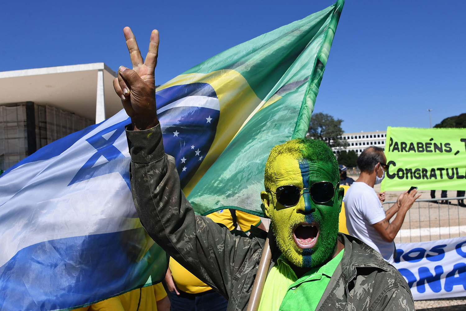 """A man shows support for Brazilian President Jair Bolsonaro during a demonstration in Brasilia on May 31. Bolsonaro has berated governors and mayors for imposing what he calls """"the tyranny of total quarantine."""" Even as his country surpassed Russia to have the world's second-highest death toll, Bolsonaro called for Brazil's football season to resume. EVARISTO SA/AFP via Getty Images"""