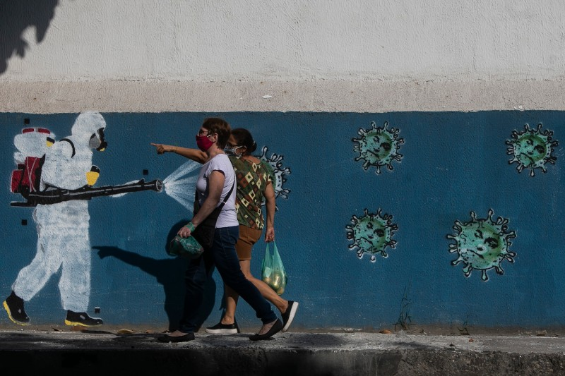 People wearing face masks walk past a wall with a graffiti depicting a cleaner in protective gear spraying viruses with the face of President Jair Bolsonaro in Estacio neighborhood on June 8, 2020 in Rio de Janeiro, Brazil.