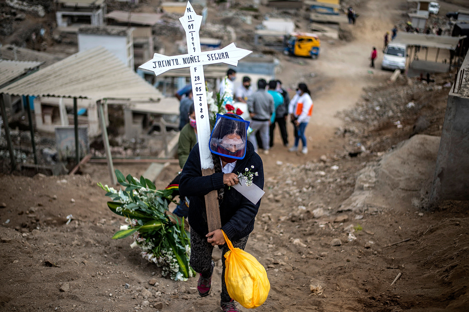 A relative of a suspected COVID-19 victim carries a cross during the burial at the Nueva Esperanza cemetery in the southern outskirts of Lima, Peru, on May 30. ERNESTO BENAVIDES/AFP via Getty Images