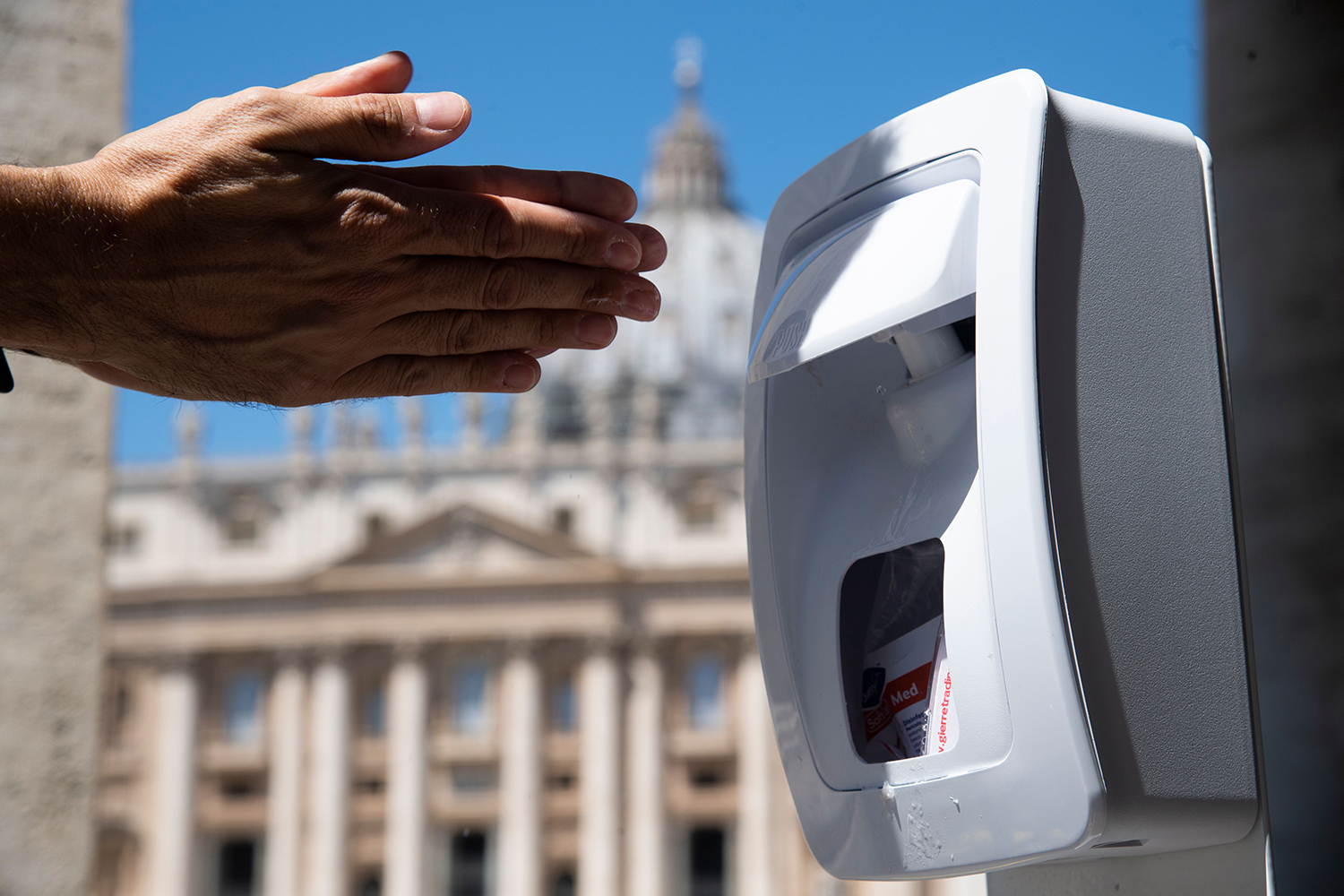 A visitor uses a hand sanitizer dispenser prior to passing through security controls at Saint Peter's Square at the Vatican to attend Pope Francis' Regina Coeli Prayer on May 31, the first public gathering there since the lockdown was imposed three months ago. TIZIANA FABI/AFP via Getty Images