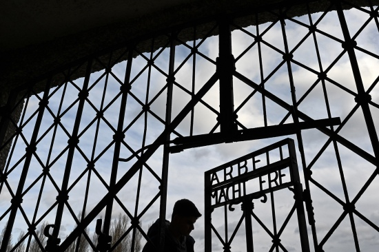 "A visitor walks through the entrance gate bearing the inscription ""Work Will Set You Free"" at the former concentration camp in Dachau, southern Germany, on Dec. 9, 2019."