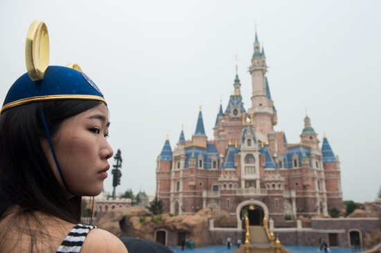 A girl wearing Mickey Mouse ears watches the opening ceremony of the Shanghai Disney Resort on June 16, 2016. In 1997 after U.S. studios released three major films that painted the Chinese Communist Party in an unflattering light, the party threatened to pull out of its planned Disney theme park.