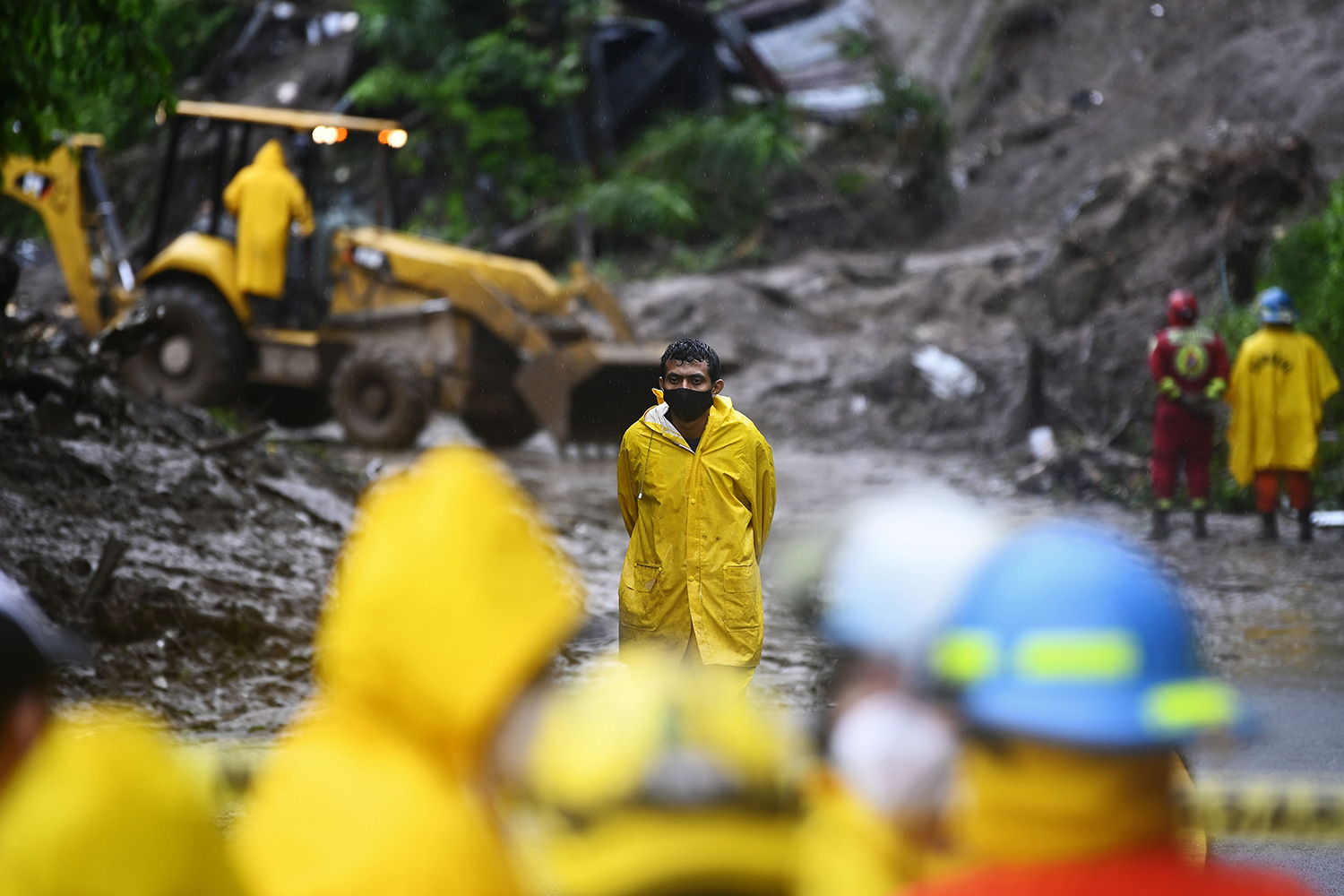 Rescuers and firefighters search for seven people who were buried by a landslide caused by Tropical Storm Cristobal in Santo Tomás, El Salvador, on June 3. MARVIN RECINOS/AFP via Getty Images