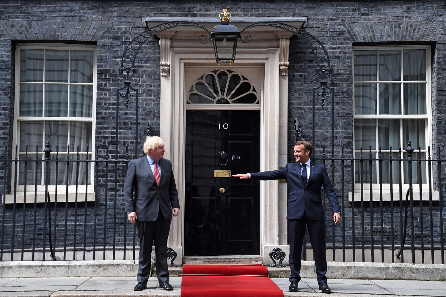 French President Emmanuel Macron (right) gestures about staying socially distant alongside British Prime Minister Boris Johnson as Macron arrives at Downing Street in central London on June 18 for a meeting. Macron was visiting London to commemorate the 80th anniversary of former French President Charles de Gaulle's appeal to French people to resist the Nazi occupation during World War II. DANIEL LEAL-OLIVAS/AFP via Getty Images